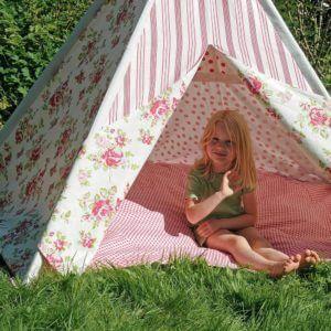 Junges Mädchen sitzt im HAB & GUT Zelt Kinderzimmer auf einer Wiese